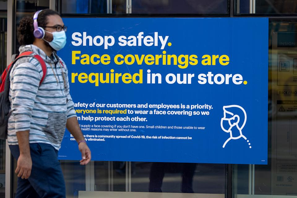 "NEW YORK, NEW YORK - SEPTEMBER 30: A man wearing a  mask walks past a ""shop safely as the city continues , face covers are required in our store"" sign outside a Best Buy in Union Square Phase 4 of re-opening following restrictions imposed to slow the spread of coronavirus on September 30, 2020 in New York City. The fourth phase allows outdoor arts and entertainment, sporting events without fans and media production. (Photo by Alexi Rosenfeld/Getty Images)"