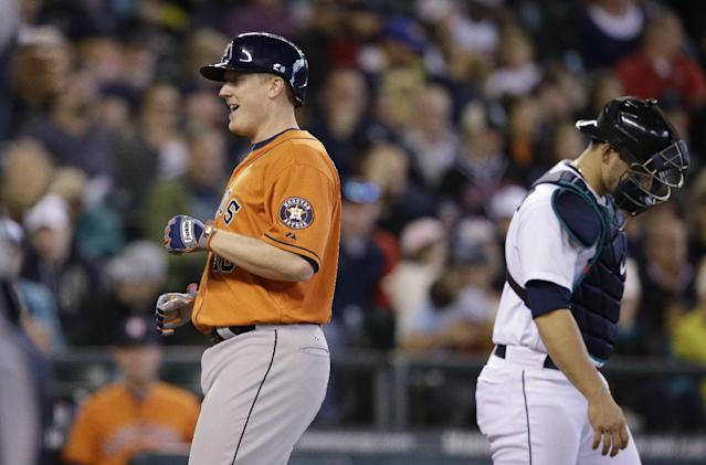 Houston Astros' Marc Krauss, left, smiles as he crosses the plate on his two-run home run in the seventh inning as Seattle Mariners catcher Mike Zunino looks away in a baseball game Sunday, May 25, 2014, in Seattle. (AP Photo/Elaine Thompson)