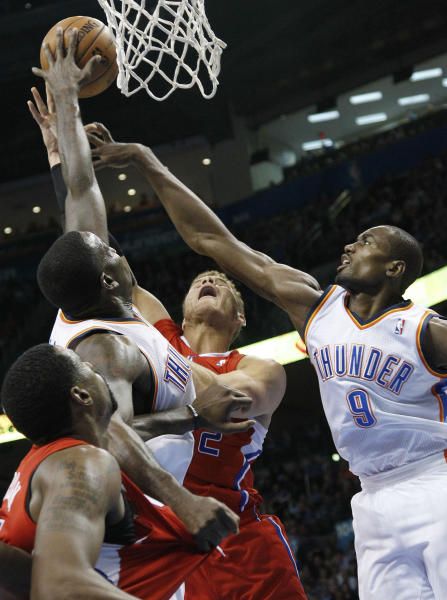 Los Angeles Clippers forward Blake Griffin, center, has his shot blocked by Oklahoma City Thunder center Kendrick Perkins, left, as he is double-teamed by Perkins and forward Serge Ibaka (9) in the first quarter of an NBA basketball game in Oklahoma City, Wednesday, Nov. 21, 2012. (AP Photo/Sue Ogrocki)