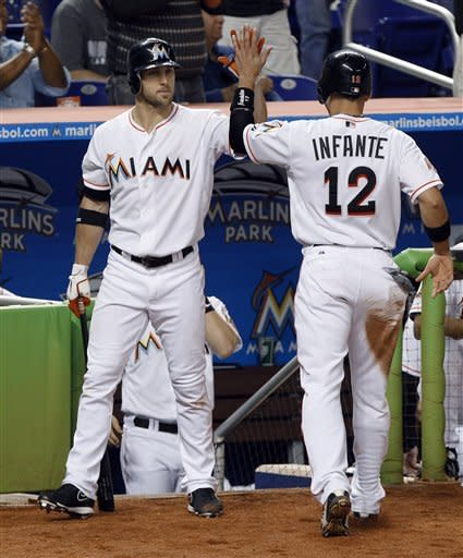 Miami Marlins' Omar Infante (12) is met by Bryan Petersen, left, after scoring in the sixth inning on a double by Giancarlo Stanton during a baseball game against the Washington Nationals, Tuesday, May 29, 2012, in Miami. (AP Photo/Lynne Sladky)