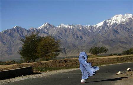 An Afghan woman in a burqa walks along a road on a windy day on the outskirts of Kabul