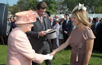 <p>Hundreds of onlookers watched as Queen Elizabeth welcomed journalist Katie Couric to her Buckingham Palace Garden Party, for which she was dressed in a mauve shift dress and white fascinator.</p>