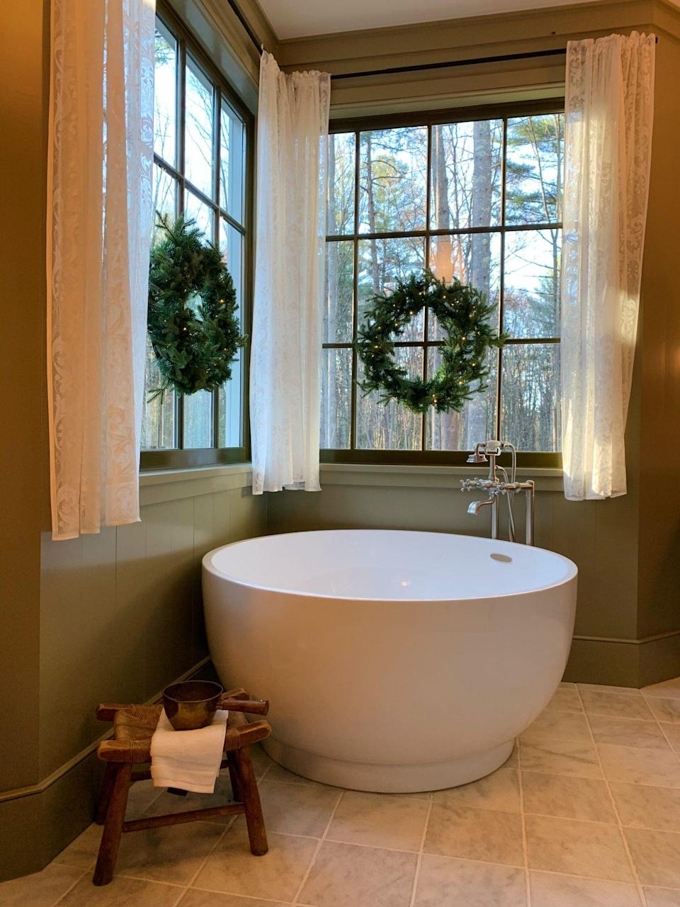 <p>A pair of pre-lit wreaths hang above the Japanese soaking tub in the main bath. </p>