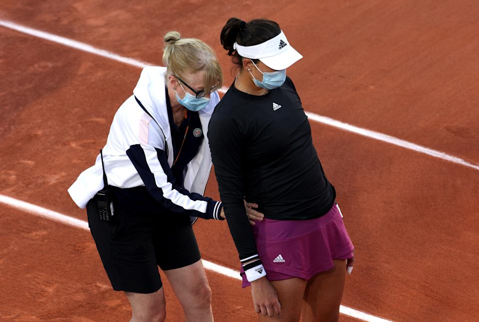PARIS, FRANCE - MAY 31: Garbine Muguruza of Spain speaks to a physic after an injury in their ladies singles first round match against Marta Kostyuk of Ukraine on day two of the 2021 French Open at Roland Garros on May 31, 2021 in Paris, France. (Photo by Adam Pretty/Getty Images)