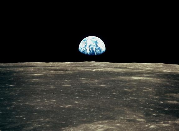 This view from the Apollo 11 spacecraft in July 1969 shows the Earth rising above the moon's horizon. The lunar terrain pictured is in the area of Smyth's Sea on the nearside.