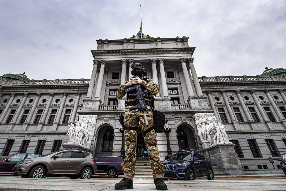 A member of the Pennsylvania Capitol Police stands guard at the entrance to the Pennsylvania Capitol Complex in Harrisburg, Pa., Wednesday, Jan. 13, 2021. State capitols across the country are under heightened security after the siege of the U.S. Capitol last week. (Jose F. Moreno/The Philadelphia Inquirer via AP)