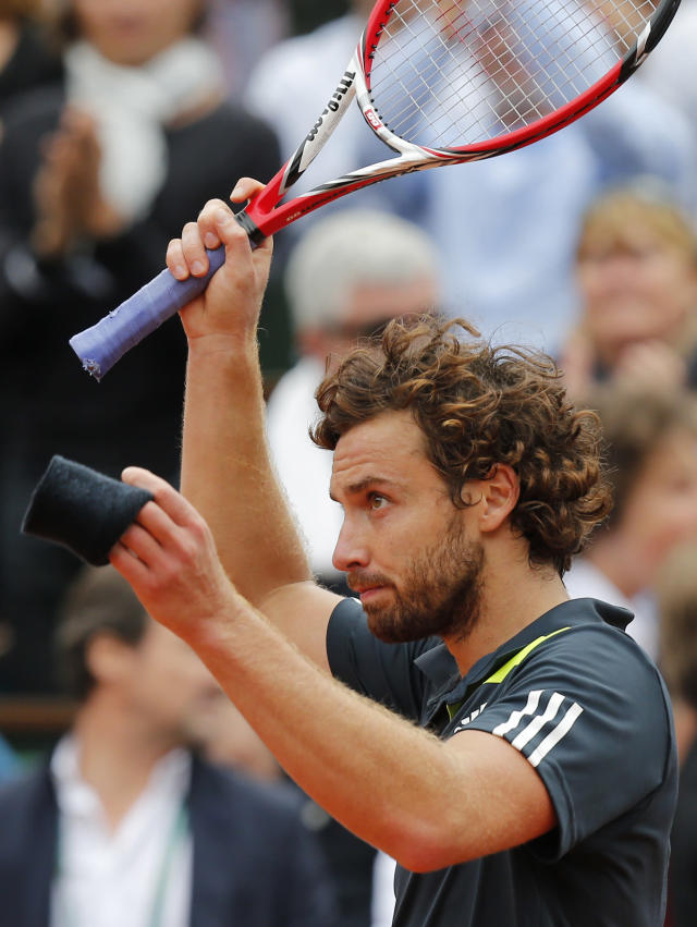 Latvia's Ernests Gulbis waves after defeating Switzerland's Roger Federer during their fourth round match of the French Open tennis tournament at the Roland Garros stadium, in Paris, France, Sunday, June 1, 2014. (AP Photo/David Vincent)