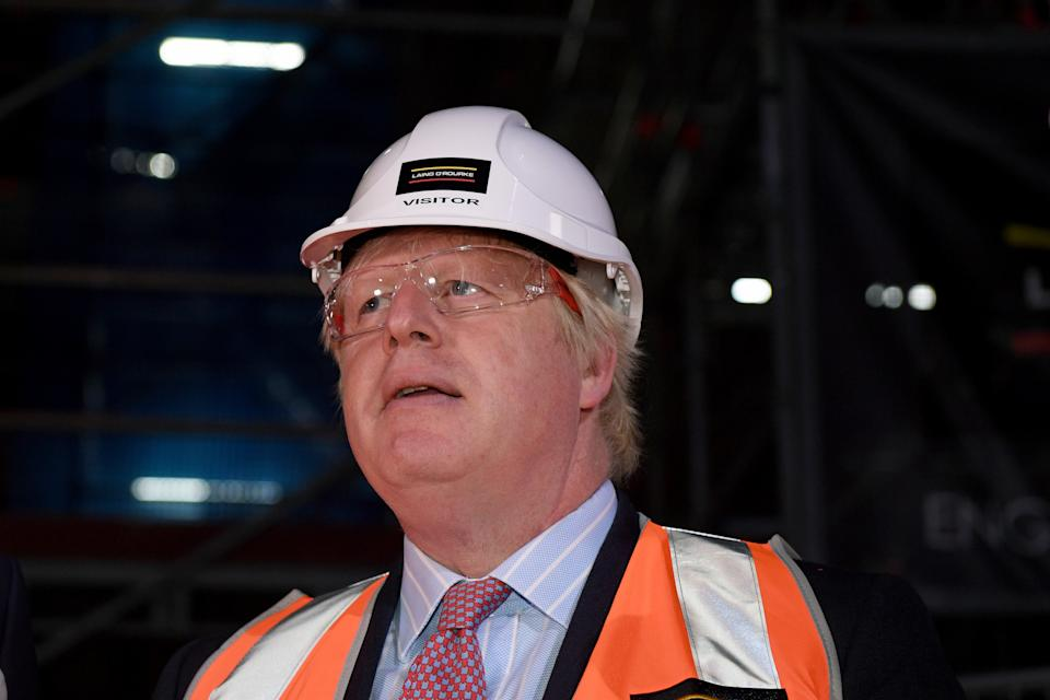 Boris Johnson wears protective eyewear and a hard hat as he tours construction work underway