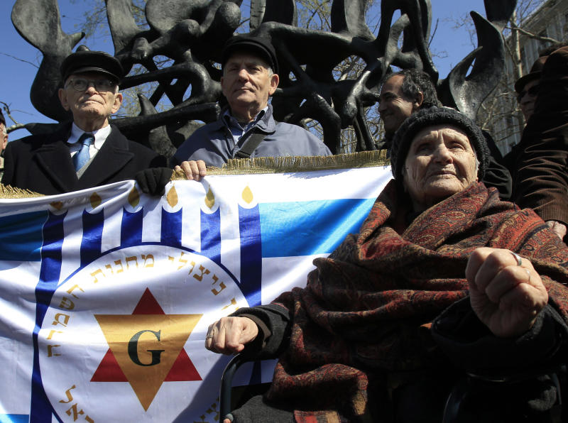 "Survivors of the concentration camps, from left Moshe Haelion, Abraham Ashkenazi and Zana Santicario Saatsoglou, hold a banner that reads in Hebrew :""The organization of death camps survivors from Greece in Israel"" in the northern port city , of Thessaloniki, Greece, on Saturday, March 16, 2013. Jewish residents in this northern Greek city have gathered to commemorate the 70th anniversary from the first roundup and deportation of Jews to Nazi extermination camps in World War II. By August 1943, 46,091 Jews had been deported to Auschwitz-Birkenau. Of those, 1,950 survived. (AP Photo/Nikolas Giakoumidis)"
