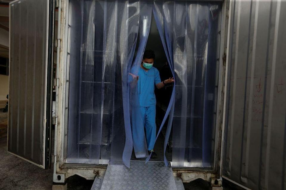 A Kepala Batas Hospital staff walks out of a container which doubles as a morgue in Penang August 20, 2021. ― Picture by Sayuti Zainudin