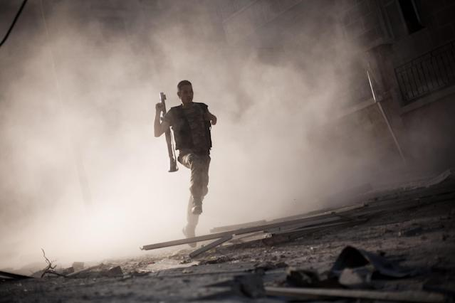 FILE - A Free Syrian Army fighter runs after attacking a tank with a rocket-propelled grenade during fighting in the Izaa district in Aleppo, Syria, Friday, Sept 7, 2012. (AP Photo/Manu Brabo, File)