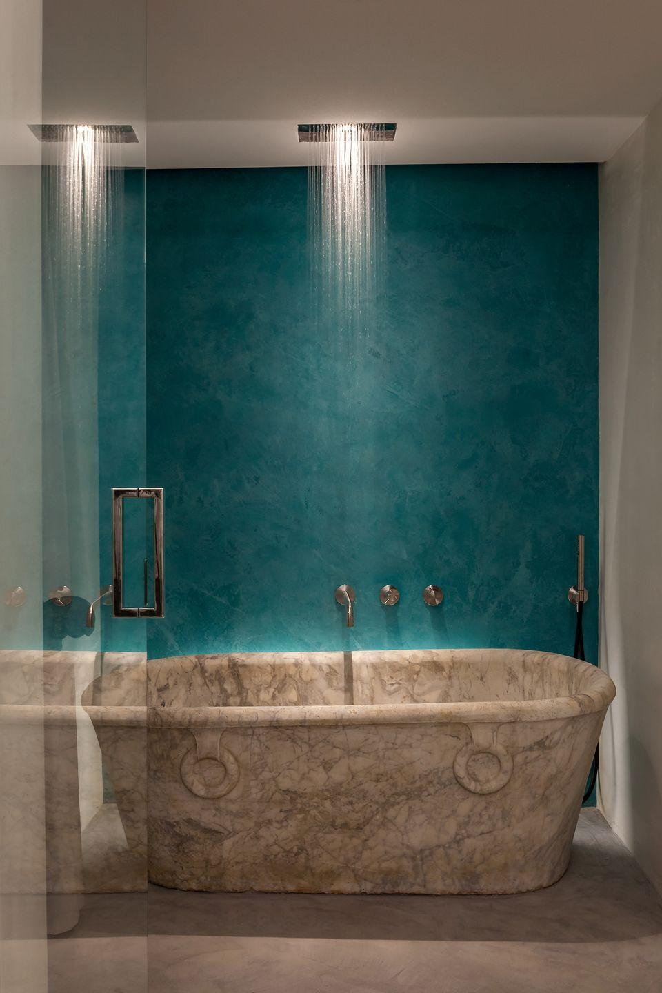 """<p>While <a href=""""https://www.veranda.com/home-decorators/g28539782/blue-paint-colors/"""" rel=""""nofollow noopener"""" target=""""_blank"""" data-ylk=""""slk:blue is a favorite wall color"""" class=""""link rapid-noclick-resp"""">blue is a favorite wall color</a> for creating a serene space, the color turquoise specifically offers a feeling of refreshment, energy, and joy. We love the rich hue featured in this <a href=""""https://www.thethinkingtraveller.com/aifaraglioni"""" rel=""""nofollow noopener"""" target=""""_blank"""" data-ylk=""""slk:Ai Faraglioni"""" class=""""link rapid-noclick-resp"""">Ai Faraglioni</a> villa on the coast of Sicily. This stunning bathroom echoes its surroundings overlooking the Mediterranean Sea and makes the dramatic marble bathtub stand out even more. </p>"""