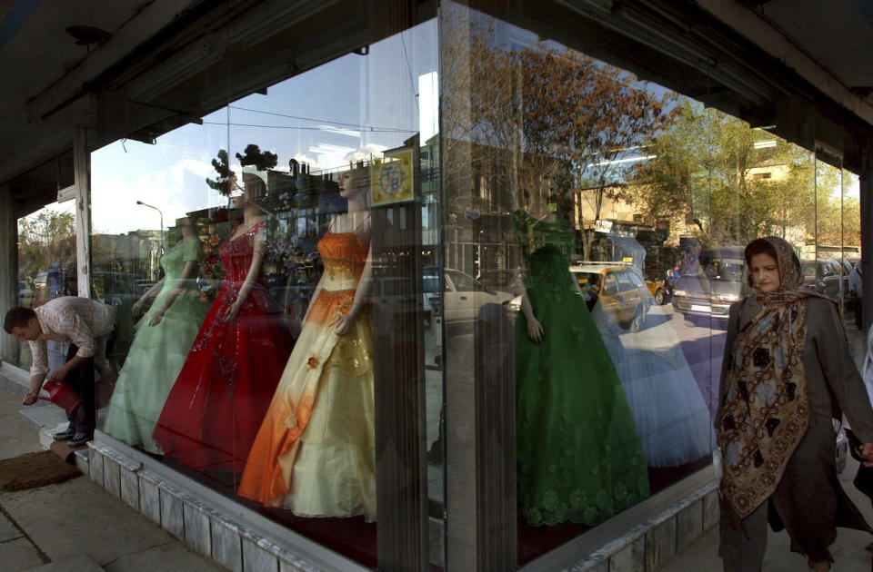 FILE -- In this June 15, 2006 file photo, an Afghan woman walks past modern dresses in Kabul, Afghanistan. The Taliban fighters who rolled into Afghanistan's capital and other cities in recent days appear awestruck by the towering apartment blocks, modern office buildings and shopping malls. When the Taliban last seized power, in 1996, the country had been ravaged by civil war and the capital was in ruins. (AP Photo/Musadeq Sadeq, File)