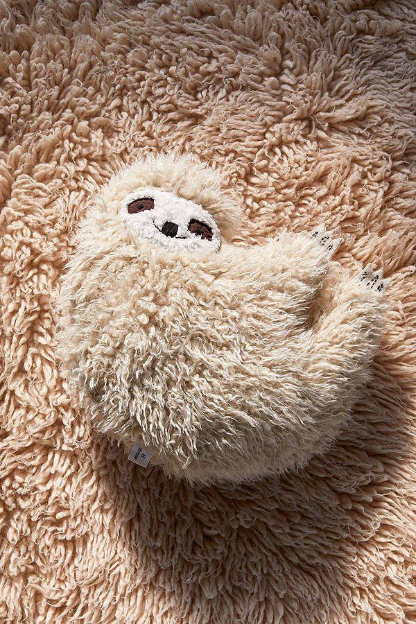 "<i>Buy it from <a href=""https://www.urbanoutfitters.com/shop/furry-sloth-pillow?category=gift-ideas-for-women&color=014&reviewPage=2"" target=""_blank"">Urban Outfitters</a> for $49.</i>"