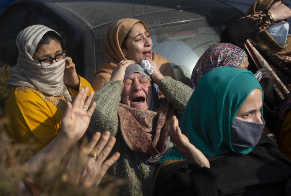 Relatives of Basharat Ahmad Zargar cry during his funeral in Srinagar, Indian-controlled Kashmir, Sunday, Feb.14, 2021. Zargar, who was working at a power project, was among the dozens killed after a part of a Himalayan glacier broke off on February 7 sending a devastating flood downriver slamming into two hydropower projects in northern India. (AP Photo/Mukhtar Khan)