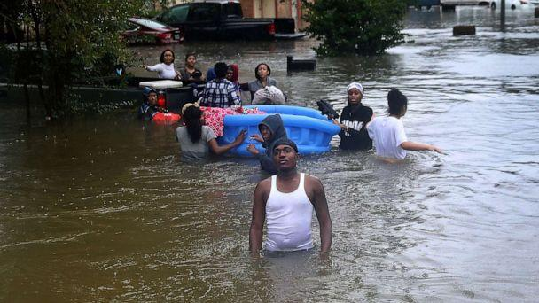 PHOTO: People walk down a flooded street as they evacuate their homes after the area was inundated with flooding from Hurricane Harvey on Aug. 28, 2017, in Houston. (Joe Raedle/Getty Images, FILE)