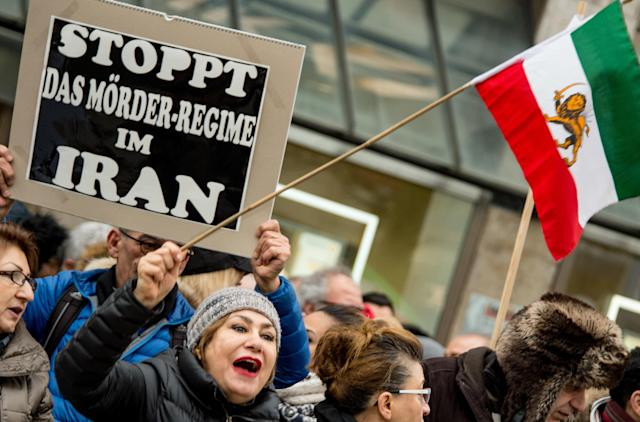 <p>A man carries a banner reading 'Stop the Iranian murder regime' at the same time as people wave the Flag of Iran (1907·1979) in Hamburg, Germany, Jan. 6,2018. (Photo: Axel Heimken/DPA via ZUMA Press) </p>