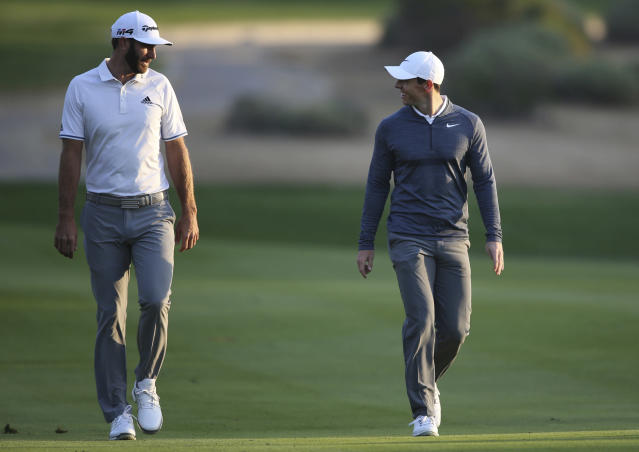 FILE - In this Jan. 18, 2018, file photo, Dustin Johnson of the United States, left, and Rory McIlroy of Northern Ireland talk on the 10th fairway during the first round of the Abu Dhabi Championship golf tournament in Abu Dhabi, United Arab Emirates. Dustin Johnson left The Players Championship two months ago and didn't play golf again until Sunday. He figured his game needed to be in shape for Rory McIlroy, his partner, in a charity match Sunday at Seminole that will be live golf's return to television. (AP Photo/Kamran Jebreili, File)