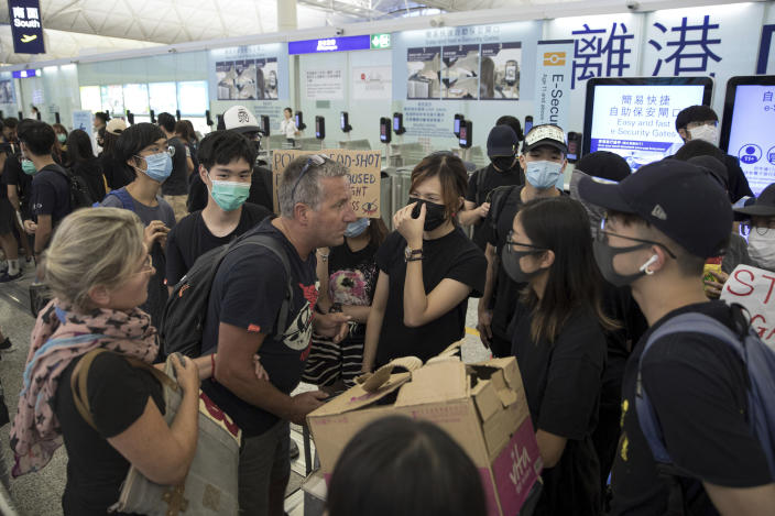 Travelers argue with protesters as they try to go through the departure gates of the Hong Kong International Airport in Hong Kong, Tuesday, Aug. 13, 2019. (Photo: Vincent Thian/AP)