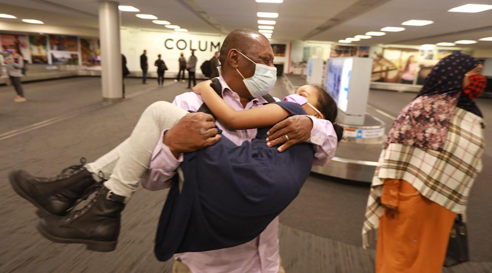 "Mohamed Salem Ali twirls his granddaughter Reem Mohammed, 6, shortly after he arrived at John Glenn International Airport in Columbus, Ohio, on April 8, 2021. Ali, a Somali man, wasn't able to join his family in Columbus due to the Trump administration's ""Muslim ban."" When Biden lifted the ban earlier this year, the family got their father a visa and he arrived in Columbus Thursday morning, April 8, 2021. At right is his wife, Fadumo Hussien."