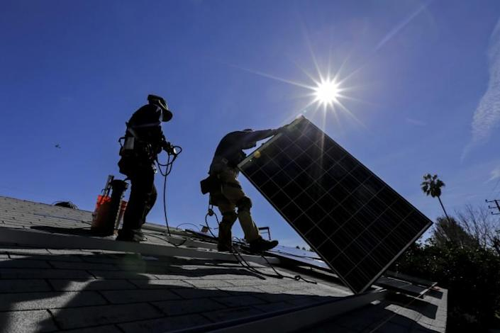 "Workers from Sunrun, a residential solar company, install solar panels at a home in Van Nuys. <span class=""copyright"">(Irfan Khan / Los Angeles Times)</span>"