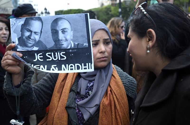 "A Tunisian demonstrator holds a placard with the photo of Tunisian journalists Sofiene Chourabi and Nadhir Ktari which reads in French ""I am Sofiene and Nadhir"" during a demonstration in Tunis on January 9, 2015 (AFP Photo/Fethi Belaid)"