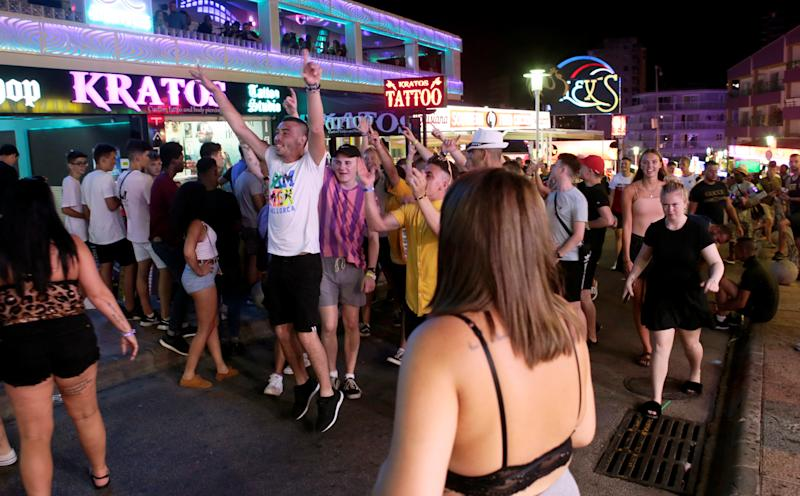 Tourists walk shouting at Punta Ballena street in Magaluf, on the Spanish Balearic island of Mallorca, Spain, August 11, 2018. REUTERS/Enrique Calvo