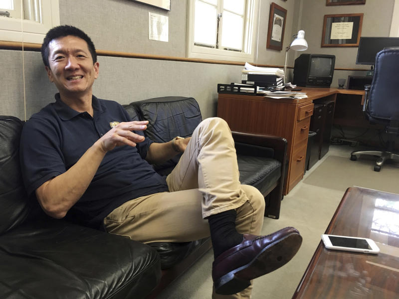 In this Friday, March 10, 2017 photo, Hawaii Attorney General Douglas Chin sits in his office in Honolulu. Hawaii was the first state to file a lawsuit challenging President Donald Trump's revised travel ban. For Chin, the son of Chinese immigrants, fighting the travel ban is personal. (AP Photo/Jennifer Sinco Kelleher)