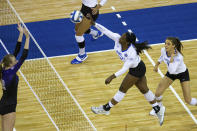 Kentucky middle blocker Azhani Tealer (15) spikes the ball against Washington middle blocker Marin Grote (12) in the first set during a semifinal in the NCAA women's volleyball championships Thursday, April 22, 2021, in Omaha, Neb. (AP Photo/John Peterson)