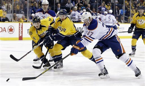 Edmonton Oilers center Lennart Petrell (37), of Finland, moves the puck past Nashville Predators defenders Kevin Klein (8) and Victor Bartley (64) during the first period of an NHL hockey game Friday, March 8, 2013, in Nashville, Tenn. (AP Photo/Mark Humphrey)
