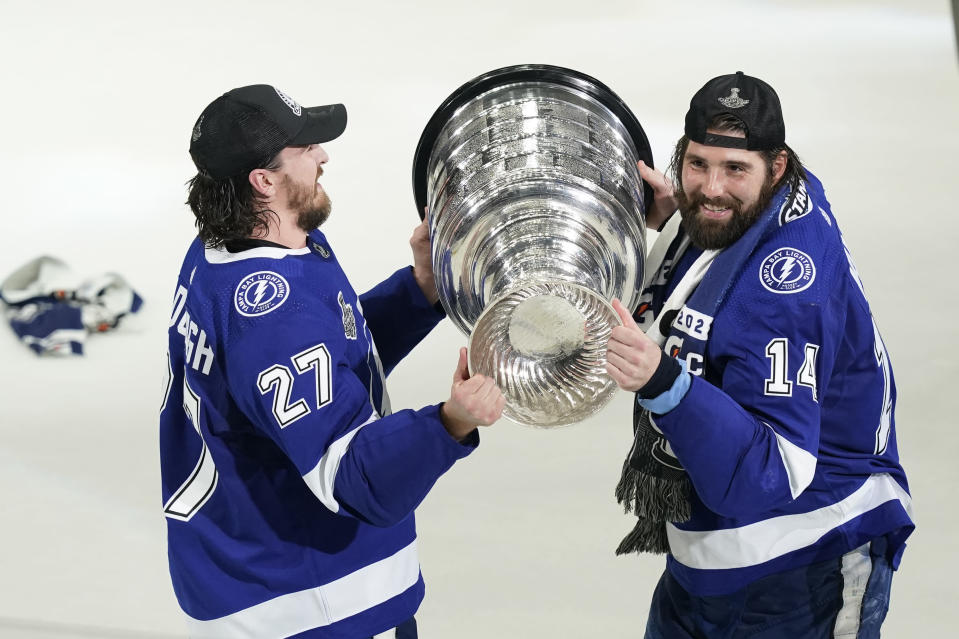 Tampa Bay Lightning defenseman Ryan McDonagh (27) hands the Stanley Cup to left wing Pat Maroon (14) after the series win in Game 5 of the NHL hockey Stanley Cup finals against the Montreal Canadiens, Wednesday, July 7, 2021, in Tampa, Fla. (AP Photo/Gerry Broome)