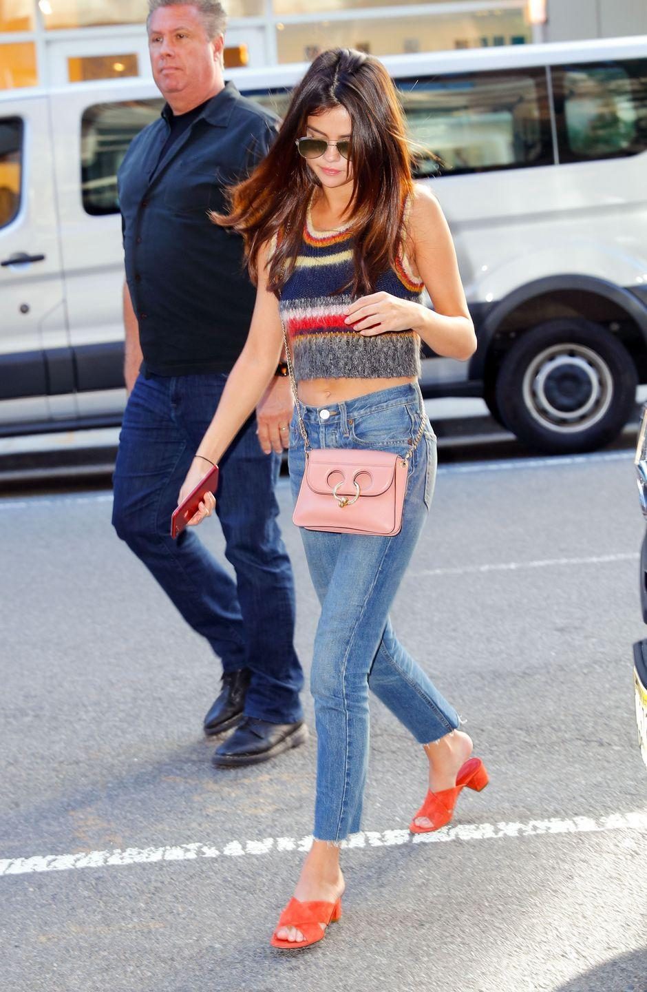 <p>The 24-year-old wore a tight pair of jeans, paired with a fuzzy, striped crop top, and orange sandals for an outing with friends in New York, June 2017. </p>