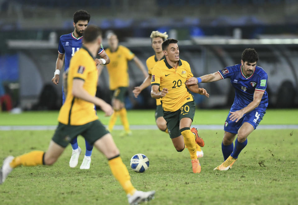 Kuwait's Khaled Ibrahim, right, fights for the ball with Australia's Chris Ikonomidis during the World Cup 2022 Group B qualifying soccer match between Kuwait and Australia in Kuwait City, Kuwait, Thursday, June 3, 2021. (AP Photo/Jaber Abdulkhaleg)