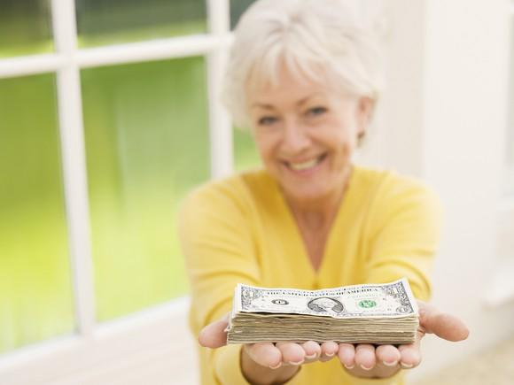 A female senior citizen holding a stack of one dollar bills in her outstretched hands.
