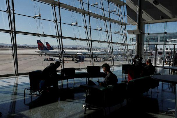 PHOTO: Travelers sit in a lounge area as Delta Air Lines planes park at a gate in McCarran International Airport in Las Vegas, Nevada, U.S., on Feb. 14, 2020. (Shannon Stapleton/Reuters)