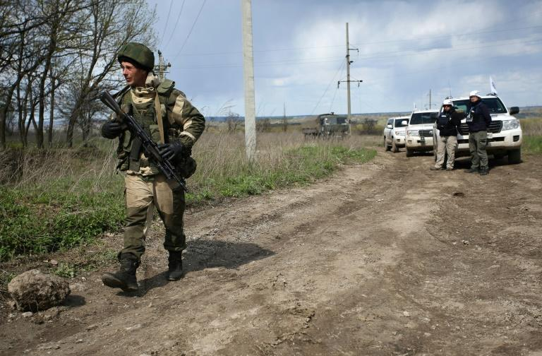 An armed pro-Russian separatist of the self-proclaimed Lugansk People's Republic walks past a convoy of the OSCE near Lugansk, on April 25, 2017