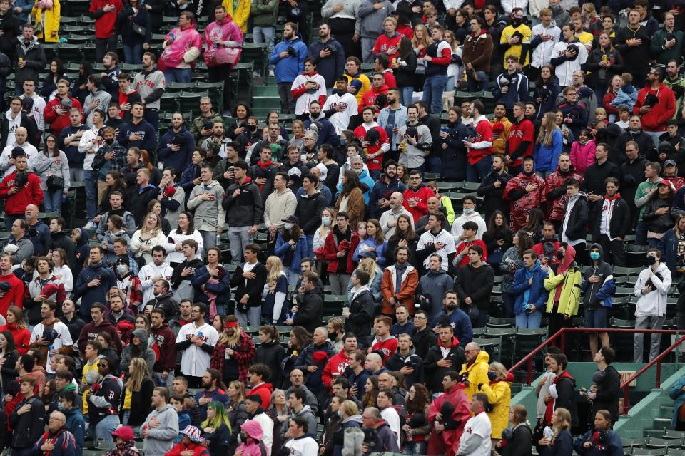 Fans stand for the national anthem before a baseball game between the Boston Red Sox and the Miami Marlins, Saturday, May 29, 2021, in Boston. Saturday marks the end of most COVID-19 restrictions in Massachusetts. (AP Photo/Michael Dwyer)