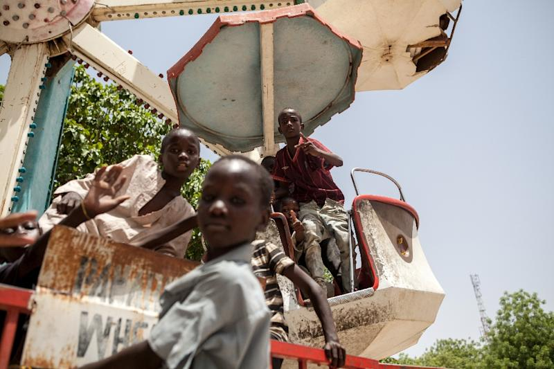 Children orphaned by Boko Haram Islamists play on a spinning wheel at an abandoned amusement park in Maiduguri, Nigeria