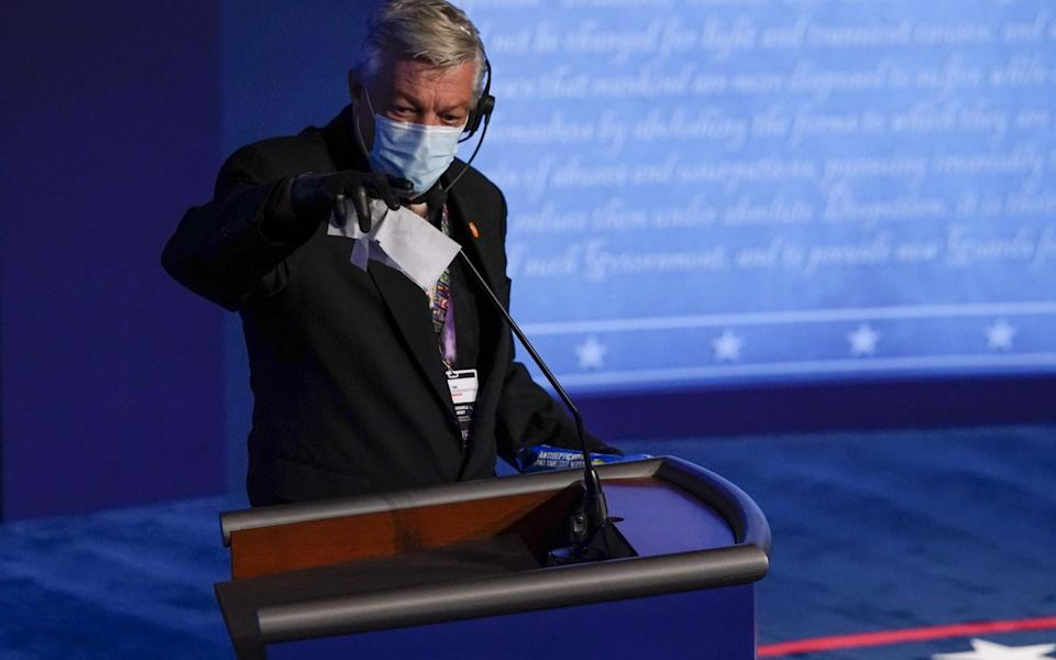 Mr Trump's podium is wiped down before the Covid-affected debate - GETTY IMAGES