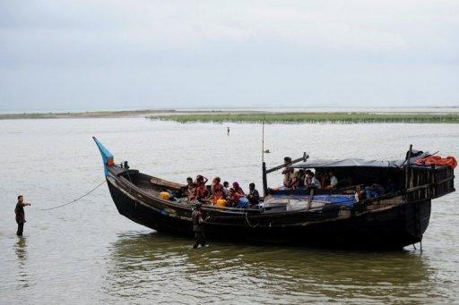 Bangladeshi Border Guards, wading in water, turn back an intercepted boat transporting Rohingya Muslims
