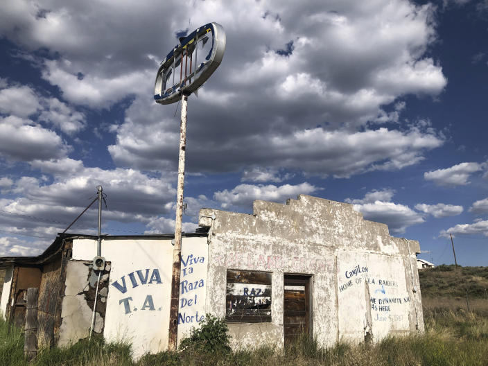In this June 28, 2020, photo, an abandoned gas station in Tierra Amarilla, N.M., is shown with graffiti honoring the 1967 courthouse raid in the town by armed Mexican American land grant activists. Activists and cities are left wondering what to do with empty spaces that once honored historic figures tied to racism as statues and monuments fall. New Mexico has no formal public art honoring the Tierra Amarilla raid, which helped spark the Chicano Movement. (AP Photo/ Russell Contreras)