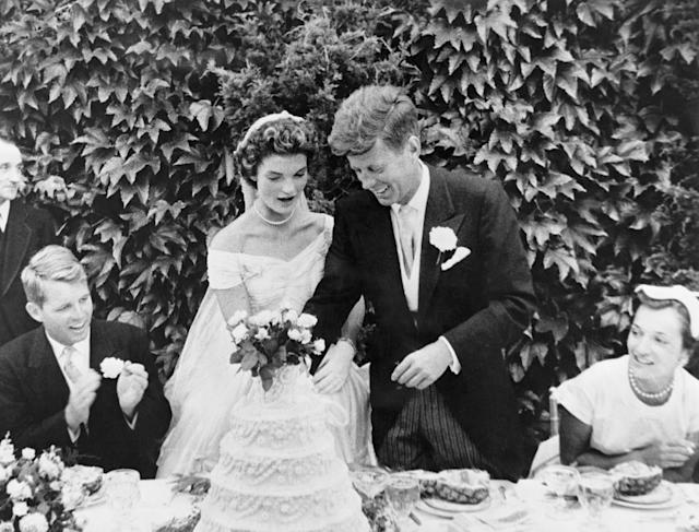 The couple cut their wedding cake at the reception. Kennedy's brother Robert Kennedy (left) looks on.