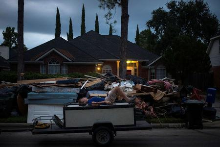A boy lies on furniture on back of trailer while passing debris from the house flooded by Tropical Storm Harvey in Houston