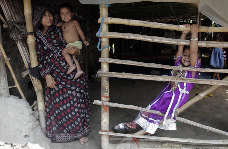 Rukhsar Khatoon, the last person in India to contract polio, hangs on to a bamboo fence, as her mother Sabeda Bibi stands beside her, at their home in Shahpara Village, 60 kilometers (40 miles) west of Kolkata, India, Thursday, March 27, 2014. In India, the scourge of polio ends with Khatoon, a lively 4-year-old girl who contracted the disease when she was a baby after her parents forgot to get her vaccinated. On Thursday, after three years with no new cases, the World Health Organization formally declared India polio-free. (AP Photo/Bikas Das)