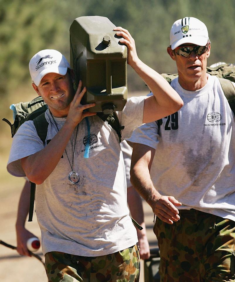 BRISBANE, AUSTRALIA - AUGUST 23:  (L-R) Michael Clarke of Australia carries a jerry can of water as coach John Buchanan looks on during an outback boot camp training session in the Beerwah State Forest on August 23, 2006 near Brisbane, Australia.  (Photo by Hamish Blair/Getty Images)