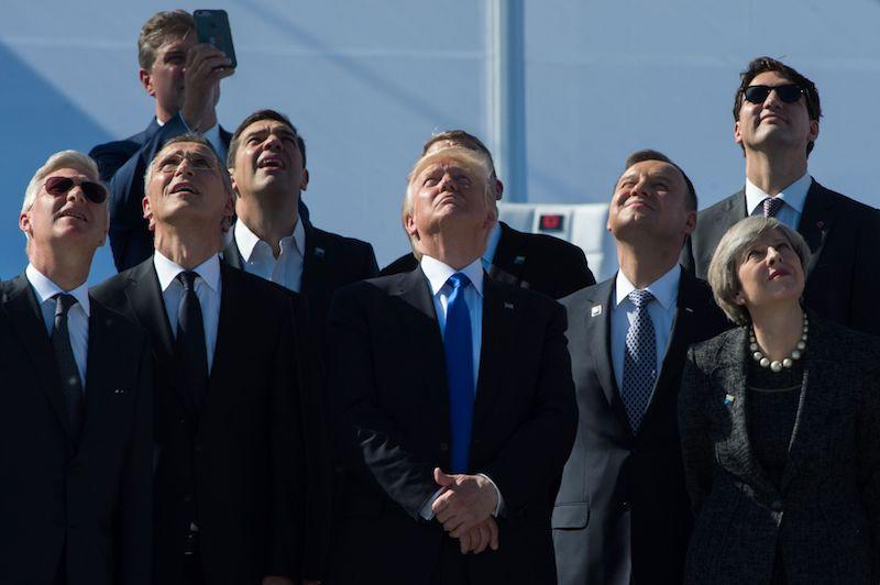 <p>Prime Minister Justin Trudeau, back right, and U.S. President Donald Trump, centre, watch planes flying overhead during a NATO meeting in Brussels on May 25, 2017. Other leaders in attendance include King Philippe of Belgium, NATO Secretary General Jens Stoltenberg, Greek Prime Minister Alexis Tsipras, UPoland's President Andrzej Duda and Britain's Prime Minister Theresa May. Photo from Getty Images. </p>