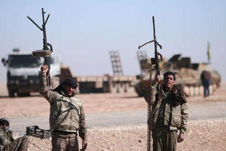 FILE PHOTO: Syrian Democratic Forces (SDF) fighters hold up their weapons in the north of Raqqa city, Syria February 3, 2017. REUTERS/Rodi Said/File Photo