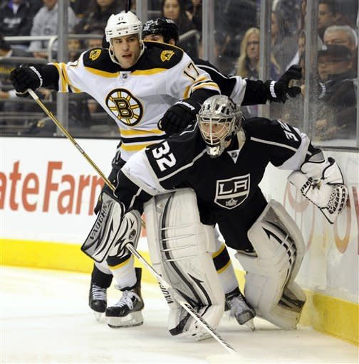 Los Angeles Kings goalie Jonathan Quick (32) keeps Boston Bruins left wing Milan Lucic (17) away from the puck in the first period of an NHL hockey game in Los Angeles, Saturday, March 24, 2012. (AP Photo/Lori Shepler)