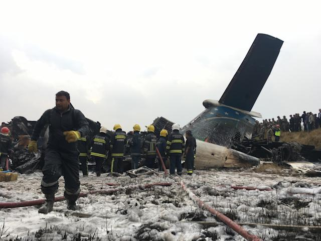 <p>Nepalese rescuers stand near a passenger plane from Bangladesh that crashed at the airport in Kathmandu, Nepal, March 12, 2018. (Photo: Niranjan Shreshta/AP) </p>