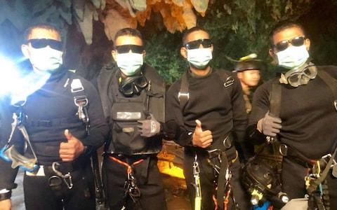 The last four Thai Navy Seals giving a thumbs up after exiting safely from the Tham Luang cave on Tuesday - Credit: AFP